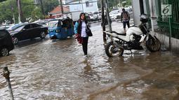 Pejalan kaki melintasi banjir yang merendam kawasan Gambir, Jakarta, Kamis (15/2). Banjir tersebut mengakibatkan jalan di sekitar lokasi terpaksa ditutup karena tidak bisa dilalui kendaraan bermotor. (Liputan6.com/Immanuel Antonius)