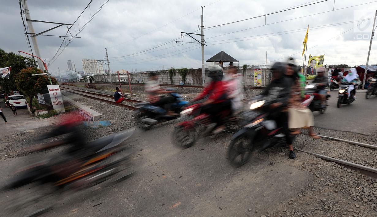 Pengendara motor melewati perlintasan kereta api tanpa palang pintu di kawasan Kelingkit, Rawa Buaya, Jakarta, Selasa (26/2). Rel kereta tanpa adanya palang pintu penutup ini sangat berbahaya karena bisa menyebabkan kecelakaan. (Liputan6.com/Johan Tallo)