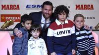 Striker Barcelona, Lionel Messi, foto bersama anak-anak saat menerima trofi Sepatu Emas Eropa di Antiga Fabrica Estrella Damm, Selasa, (18/12/2018). Messi berhak atas penghargaan itu berkat koleksi 34 gol dari 36 pertandingan. (AFP/Lluis Gene)