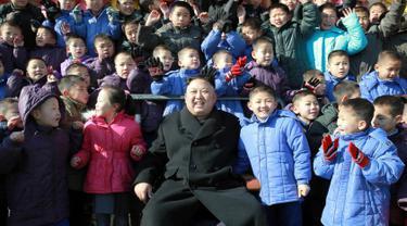 Pemimpin Korut, Kim Jong Un foto bersama dengan anak-anak yatim saat mengunjungi Sekolah Dasar Anak Yatim di Pyongyang, Korea Utara (2/2). (AFP Photo / KCNA VIA KNS / STR)