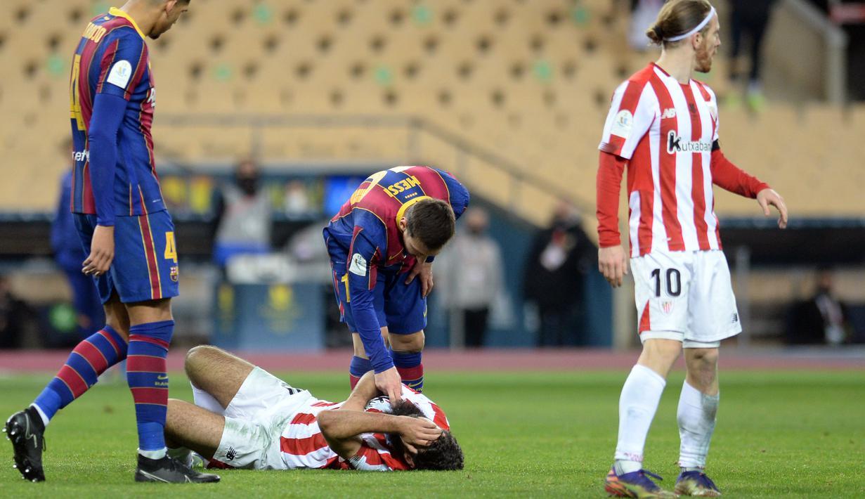 Penyerang Barcelona, Lionel Messi memeriksa penyerang Athletic Bilbao, Asier Villalibre setelah memukulnya pada pertandingan final Piala Super Spanyol di stadion La Cartuja, Senin (18/1/2021). Dalam laga tersebut, Messi menerima kartu merah setelah memukul Asier Villalibre. (AFP/Cristina Quicler)