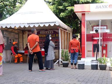 Warga antre untuk melakukan penarikan uang bantuan sosial tunai (BST) di ATM Bank DKI di Jakarta, Selasa (20/7/2021). Pemprov DKI Jakarta resmi mencairkan BST kepada warga DKI Jakarta. (Liputan6.com/Angga Yuniar)