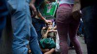 Perempuan pingsan saat antre makanan. Hidup kian tak menentu di Venezuela di tengah krisis ekonomi yang terjadi (AP PHOTO / ARIANA CUBILLOS)