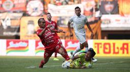 Gelandang Persija Jakarta, Riko Simanjuntak, berebut bola dengan kiper PSS Sleman, Ega Rizky, pada laga Liga 1 2019 di Stadion Patrioti, Rabu (3/7). (Bola.com/Yoppy Renato)