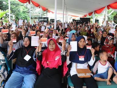 Warga menunjukkan kartu keluarga sejahtera saat Penyaluran Bantuan Sosial Program Keluarga Harapan (PKH) tahun 2019 dan Bantuan Pangan Non Tunai (BPNT) di Depok, Jawa Barat, Selasa (12/2). (Liputan6.com/Herman Zakharia)