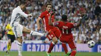 Cristiano Ronaldo melakukan tembakan mematikan melewati adangan para pemain Bayern Munchen pada leg kedua perempatfinal Liga Champions di Santiago Bernabeu stadium, Madrid, (18/4/2017). Ronaldo cetak tiga gol. (AP/Francisco Seco)
