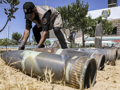 Seorang ahli bahan peledak Hamas menunjukkan proyektil yang tidak meledak setelah konflik Mei 2021 dengan Israel di kantor polisi setempat di Khan Yunis, Jalur Gaza, Sabtu (5/6/2021). Perang 11 hari antara Hamas dan Israel menewaskan 254 orang Palestina dan 12 orang Israel. (MAHMUD HAMS/AFP)