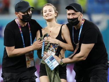 Petugas keamanan stadion menghentikan seorang penyusup lapangan wanita ketika pertandingan sepak bola Grup B UEFA EURO 2020 antara Finlandia melawan Belgia di Stadion Krestovsky, Saint Petersburg, Rusia, pada 21 Juni 2021. (AFP/Pool/Anatoly Maltsev)