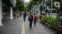 Pekerja kantoran berjalan di trotoar Jalan Sudirman, Jakarta Pusat, Rabu (6/1/2021). Selama pembatasan sosial berskala besar (PSBB) di wilayah Jawa dan Bali pada 11-25 Januari 2021, aktivitas bekerja di kantor diperketat dengan sistem work from home (WFH) 75 persen. (Liputan6.com/Faizal Fanani)