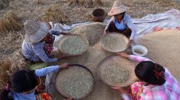 Sejumlah petani bekerja mengayak padi di sawah di Naypyitaw, Myanmar, (9/11). Di bawah pentadbiran British, Myanmar adalah negara pengeksport terbesar di dunia beras.  (AP Photo / Aung Shine Oo)