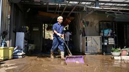 Penduduk membersihkan lumpur dari sebuah rumah setelah banjir surut di distrik Shibata, Prefektur Miyagi, Minggu (13/10/2019). Topan dahsyat Hagibis yang menerjang sejumlah wilayah di Jepang menyebabkan banjir di beberapa lokasi. (Photo by CHARLY TRIBALLEAU/ AFP)