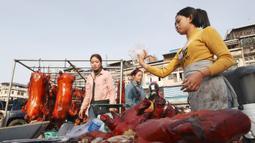 Pedagang menyiapkan babi panggang untuk perayaan Tahun Baru Imlek di Phnom Penh, Kamboja, Jumat (24/1/2020). Olahan daging babi menjadi salah satu makanan khas Imlek dan disantap oleh keluarga besar. (AP photo/Heng Sinith)