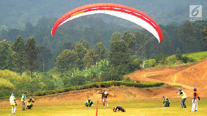 Atlet paralayang Indonesia Aris Aporiansyah saat nomor ketepatan mendarat (KTM) individual di Gunung Mas, Bogor (21/8). Hingga saat ini pertandingan pada berbagai nomor di paralayang Asian Games 2018 masih berlangsung. (Merdeka.com/Arie Basuki)