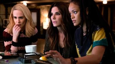 Penyanyi Rihanna (kanan) beradu akting dengan aktris Sarah Paulson dan Sandra Bullock dalam adegan film Ocean's 8. Film komedi Amerika bergenre heist ini disutradarai Gary Ross dan Olivia Milch sebagai co-writer. (Barry Wetcher/Warner Bros via AP)