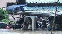 Warga dan anak-anak berada di depan rumah yang terendam banjir di Rantau Panjang, timur laut Malaysia, Selasa (3/1). Akibat hujan lebat yang turun terus menerus selama empat hari di Malaysia, 5.000 warga terpaksa dievakuasi. (AFP PHOTO/STR/Malaysia OUT)