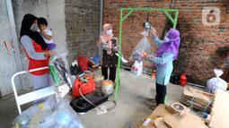 Pekerja menimbang sampah rumah tangga di bank sampah Gepe Two, Perumahan Griya Pamulang II, Tangerang Selatan, Banten, Rabu (23/12/2020). Bank sampah ini bertujuan untuk mengurangi volume sampah rumah tangga ke TPA dan menambah perekonomian keluarga melalui tabungan sampah. (merdeka.com/Arie Basuki)
