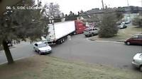 Pengemudi sebuah truk trailer yang sedang berbelok di persimpangan tidak menyadari bahwa truknya telah menyeret mobil parkir.
