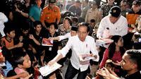 Presiden Joko Widodo atau Jokowi bersama Gubernur NTB Tuan Guru Bajang (TGB) Zainul Majdi membagikan buku saat mengunjungi korban gempa di lapangan Desa Madayin, Sambelia, Lombok Timur, NTB, Senin (30/7). (Agus Suparto/Indonesian Presidential Palace/AFP)