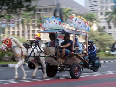 Delman hias membawa penumpang melintasi Jalan Medan Merdeka Selatan, Jakarta, Selasa (19/6). Masa libur Lebaran 2018 dimanfaatkan sejumlah warga untuk berwisata di sekitar Monumen Nasional dengan menaiki delman hias. (Liputan6.com/Helmi Fithriansyah)