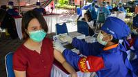 Seorang wanita menerima vaksin virus corona COVID-19 AstraZeneca di Denpasar, Bali, Sabtu (26/6/2021). Ratusan warga terlihat antusias mengikuti vaksinasi massal tersebut. (SONY TUMBELAKA/AFP)
