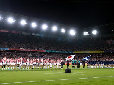Pemain rugby Jepang dan Skotlandia berdoa bersama selama satu menit untuk korban Topan Hagibis sebelum Pertandingan Pool A Piala Dunia Rugbi 2019 di Stadion Internasional Yokohama (13/10/2019). (AFP Photo/Odd Andersen)