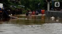 Warga melewati banjir yang menggenangi Jalan Jatinegara Barat, Jakarta, Kamis (2/1/2020). Hujan yang terjadi kemarin malam membuat Kali Ciliwung meluap ke jalan. (merdeka.com/Imam Buhori)