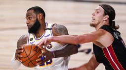 Pebasket Miami Heat, Kelly Olynyk, berebut bola dengan pebasket Los Angeles Lakers, LeBron James, pada laga Gim ketiga Final NBA, Senin (5/10/2020). Miami Heat menang dengan skor 115-104. (AP Photo/Mark J. Terrill)