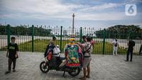 Pedagang kaos cendera mata keliling mencoba peruntungan dari para pengunjung yang ingin menyaksikan Tugu Monas Jakarta dari balik pagar, Sabtu (2/1/2021). (Liputan6.com/Faizal Fanani)