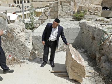 Petugas keamanan dan seorang Yahudi Ortodoks memeriksa sebuah batu besar yang jatuh dari Tembok Ratapan dua hari sebelumnya di Kota Tua Yerusalem, Rabu (25/7). Bongkahan batu itu nyaris menimpa seorang peziarah yang sedang berdoa. (AFP/AHMAD GHARABLI)