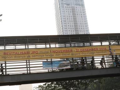Spanduk peringatan revitalisasi Jembatan Penyeberangan Orang (JPO) di JPO Jalan Sudirman, Jakarta, Selasa (6/11). Pemprov DKI Jakarta berencana merevitalisasi tiga JPO di sepanjang Jalan Jenderal Sudirman. (Liputan6.com/Immanuel Antonius)
