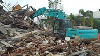 Sejumlah alat berat tengah melakukan evakuasi dan pembersihan puiang-puing Kantor Gubernur Sulawesi Barat Pasca Gempa Bumi dengan Magnitudo 6,2 mengguncang Majene pada Jumat 15 Januari 2021. (Liputan6.com/Abdul Rajab Umar)