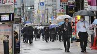 Warga memakai masker untuk melindungi dari penyebaran virus corona berjalan di jalan yang dipenuhi bar dan restoran di Tokyo (8/3/2021). Pemerintah Jepang memperpanjang keadaan darurat di wilayah Tokyo hingga 21 Maret karena sistem medis masih disaring oleh pasien COVID-19. (AP Photo/Koji Sasahara)