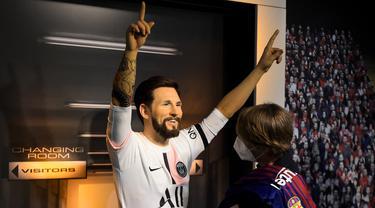 Seorang tim potret museum lilin Madame Tussauds Berlin, Karen Fries (kanan) memperbaiki jersey baru Paris Saint-Germain (PSG) pada patung lilin Lionel Messi di Berlin. (11/7/2021). Messi resmi bergabung dengan PSG dari Barcelona setelah menandatangani kontrak dua tahun. (AFP/Tobias Schwarz)