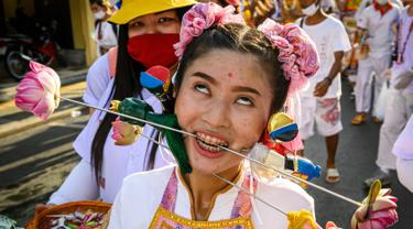 Seorang wanita menusuk pipinya dengan besi  saat mengikuti prosesi perayaan Festival Vegetarian tahunan di Phuket, Thailand, Kamis (3/10/2019). Festival ini biasanya berlangsung selama 9 hari di akhir September sampai Oktober. (AFP Photo/Mladen Antonov)
