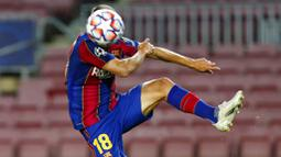 Bek Barcelona, Jordi Alba, menyundul bola saat melawan Dynamo Kiev pada laga Liga Champions di Stadion Camp Nou, Kamis (5/11/2020). Barcelona menang dengan skor 2-1. (AP/Joan Monfort)