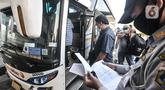 Petugas memeriksa dokumen dan SIKM penumpang sebelum berangkat dari Terminal Pulogebang, Senin (10/5/2021). Petugas Terminal Pulogebang mencatat hingga sore ini terdapat 16 penumpang dan 4 bus AKAP yang berangkat dengan tujuan kota-kota di Jawa Tengah, Timur dan Madura. (merdeka.com/Iqbal S Nugroho)