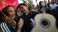 Suporter Meksiko memainkan gitar saat merayakan kemenangan timnya atas Jerman pada Piala Dunia 2018 di Luzhniki Stadium, Moskow, (17/6/2018). Meksiko menan 1-0. (AP/Alexander Zemlianichenko)