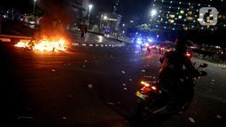 Api membakar sejumlah barang usai demonstrasi yang berujung anarkis di kawasan Bundaran HI, Jakarta, Kamis (8/10/2020). Massa membakar sejumlah barang saat demonstrasi menolak pengesahan UU Cipta Kerja. (Liputan6.com/Faizal Fanani)