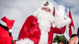 Santa Claus melambaikan tangan setibanya Kongres Dunia Sinterklas di Kopenhagen, Denmark, Senin (23/7). Kegiatan itu merupakan sarana dimana seluruh santa di dunia bisa bertemu dan melakukan aktivitas bersama. (Mads Claus Rasmussen/Scanpix via AP)