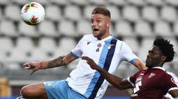 Gelandang Lazio, Sergej Milinkovic, berebut bola dengan pemain Torino pada laga lanjutan Serie A pekan ke-29 di Stadion Olimpico Grande Torino, Rabu (1/7/2020) dini hari WIB. Lazio menang 2-1 atas Torino. (AFP/Isabella Bonotto)