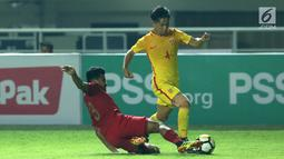 Bek Timnas Indonesia U-19, Asnawi Mangkualam (kiri) berusaha menahan pemain China U-19, Junwei Yu pada laga PSSI 88th U-19 International Tournament di Stadion Pakansari, Cibinong, Selasa (25/9). Indonesia kalah 0-3. (Liputan6.com/Helmi Fithriansyah)