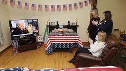 Veronica McKevitt (duduk), sepupu jauh Presiden terpilih Joe Biden, dan putri-putrinya Andrea McKevitt, dan Ciara bertepuk tangan di rumah mereka saat menyaksikan pelantikan Joe Biden di Louth, Irlandia  (20/1/2021). Joe Biden akan didampingi Wakil Presiden Kamala Harris. (Brian Lawless/PA via AP)