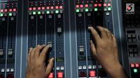 Operator mengatur gelombang suara saat presenter menyiarkan program luar negeri di Studio Voice Of Indonesia RRI, Jakarta, Rabu (11/9/2019). Hari lahir RRI pada 11 September 1945 ditetapkan sebagai Hari Radio Nasional untuk menghargai jasa para penyiar terdahulu. (merdeka.com/Iqbal Nugroho)