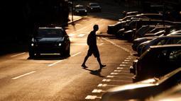 Seorang pria melintasi jalan saat matahari terbenam di Beograd, Serbia, Kamis (2/7/2020). (AP Photo/Darko Vojinovic)