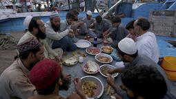 Nelayan berbuka puasa selama bulan suci Ramadhan, di galangan kapal, di Karachi, Pakistan, Selasa (20/4/2021). (AP Photo / Fareed Khan)