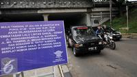 Kendaraan melintas di lokasi pemasangan papan sosialisasi uji coba pembatasan lalu lintas ganjil-genap di Jakarta, Senin (25/7). Penerapan sistem ganjil-genap akan dimulai pada 27 Juli hingga 26 Agustus 2016. (Liputan6.com/Yoppy Renato)