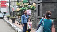 Beberapa pengunjung di kawasan perkotaan Garut, Jawa Barat sengaja berhenti sejenak untuk berfoto ria di samping balon sky dancer yang diluncurkan Kodim 0611 Garut, untuk mengingatkan masyarakat menjaga protokol kesehatan. (Liputan6.com/Jayadi Supriadin)