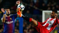 Pemain Girona, Jonas Ramalho (kanan) berusaha membuang bola dari kejaran penyerang Barcelona, Luis Suarez pada pertandingan La Liga Spanyol di stadion Camp Nou (25/2). Barcelona menang telak 6-1 atas Girona. (AP Photo/Manu Fernandez)