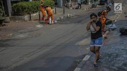 Warga menutupi matanya untuk menghindari sisa gas air mata pasca bentrok massa dengan aparat di Palmerah, Jakarta, Kamis (26/9/2019). Banyak masyarakat yang melintas dan warga sekitar perih pada mata hingga bersin akibat sisa gas air mata pasca bentrokan kemarin. (Liputan6.com/Faizal Fanani)