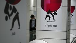 Seorang pria yang mengenakan masker pelindung untuk mencegah penyebaran virus corona berjalan di depan iklan Olimpiade Tokyo 2020 di Tokyo, Rabu (17/3/2021). Ibukota Jepang mengonfirmasi lebih dari 400 kasus virus korona baru pada hari Rabu. (AP Photo/Eugene Hoshiko)